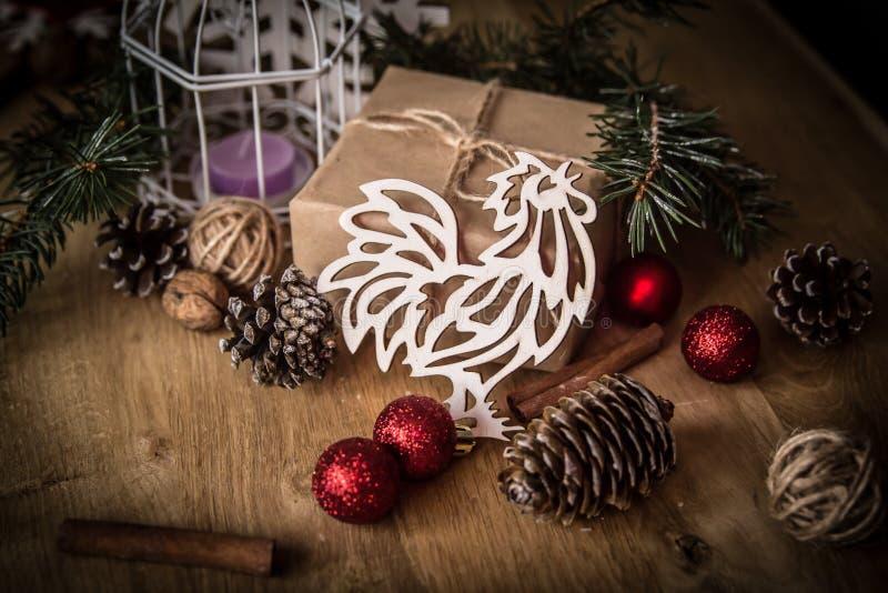 Tarjeta de Navidad pollo de papel y una caja con el regalo en fondo de la Navidad foto de archivo libre de regalías