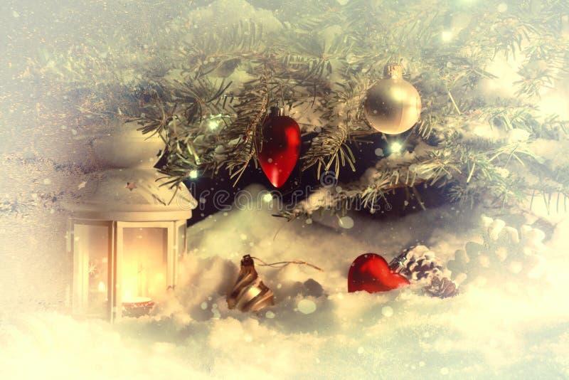Tarjeta de Navidad - una linterna en la nieve debajo de un árbol de navidad adornado con las luces y las decoraciones de la Navid imágenes de archivo libres de regalías