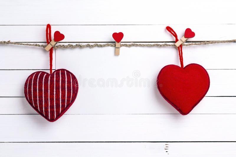 Tarjeta de papel en blanco con los corazones rojos que cuelgan en pinzas en el fondo de madera blanco Espacio para el texto imagenes de archivo