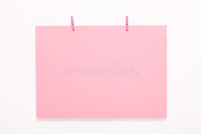 Tarjeta de papel en clavija de ropa en el fondo blanco fotografía de archivo