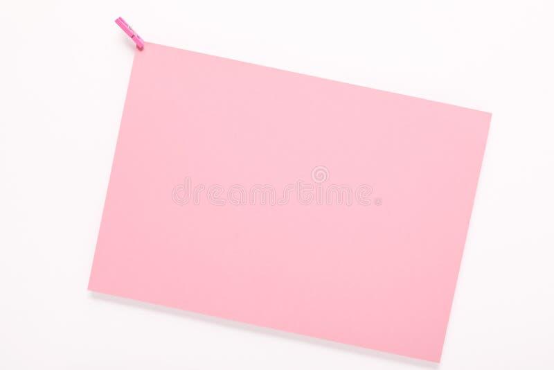 Tarjeta de papel en clavija de ropa en el fondo blanco fotos de archivo