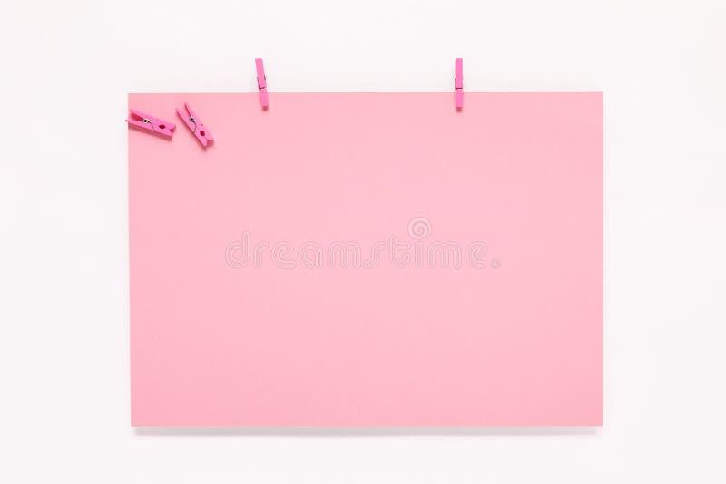 Tarjeta de papel en clavija de ropa en el fondo blanco imagenes de archivo