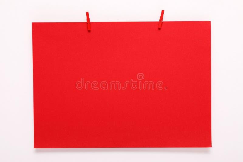 Tarjeta de papel en una clavija de ropa en un fondo blanco imágenes de archivo libres de regalías