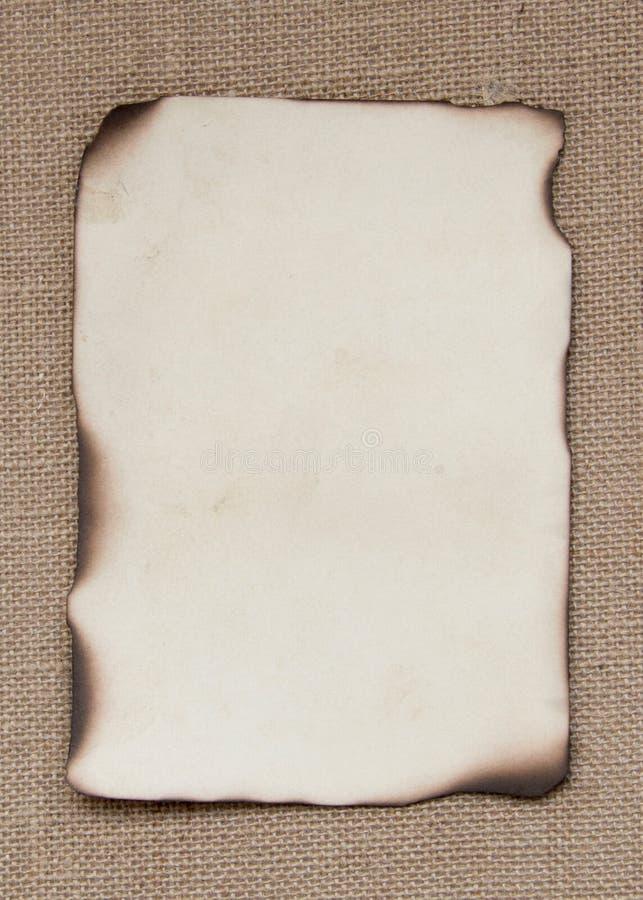 Tarjeta de papel quemada sobre la arpillera imagen de archivo libre de regalías