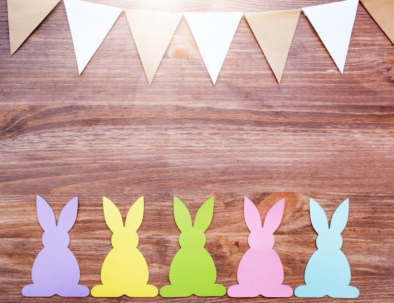 Tarjeta de pascua con los conejos y las banderas de la guirnalda en fondo de madera fotos de archivo libres de regalías