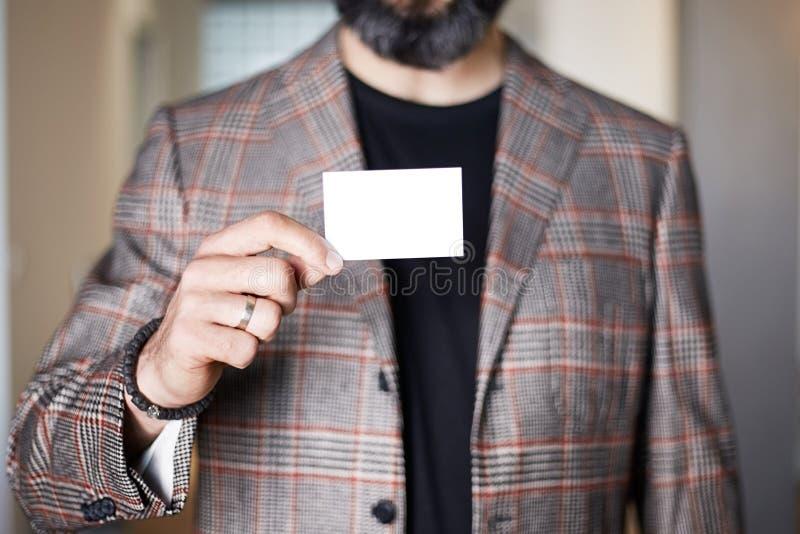 Tarjeta de visita blanca vacía del hombre de negocios de la mano barbuda de la tenencia en fondo borroso Anuncio en blanco de la  imagen de archivo libre de regalías