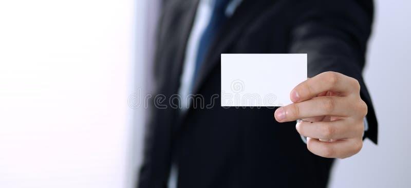 Tarjeta de visita desconocida de la tenencia de la mano del hombre de negocios con el espacio vacío, primer imagen de archivo libre de regalías