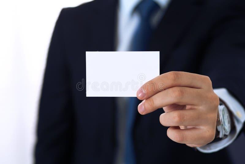Tarjeta de visita desconocida de la tenencia de la mano del hombre de negocios con el espacio vacío, primer foto de archivo libre de regalías