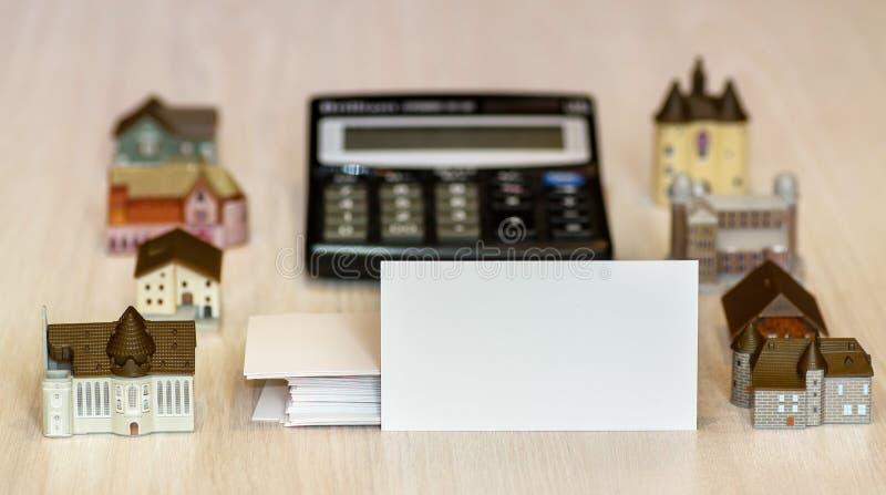 Tarjeta de visita en blanco, casas falsas y calculadora propiedades inmobiliarias, construcción, arrendando fotos de archivo libres de regalías