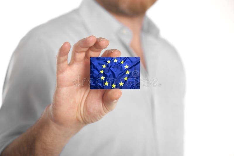 Tarjeta de visita de la tenencia del hombre de negocios con la bandera de unión europea imagen de archivo libre de regalías