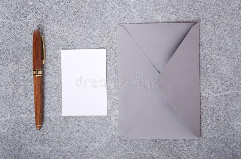 Tarjeta de visita vacía, pluma elegante y sobre Vista superior del negocio inmóvil en la tabla gris fotografía de archivo