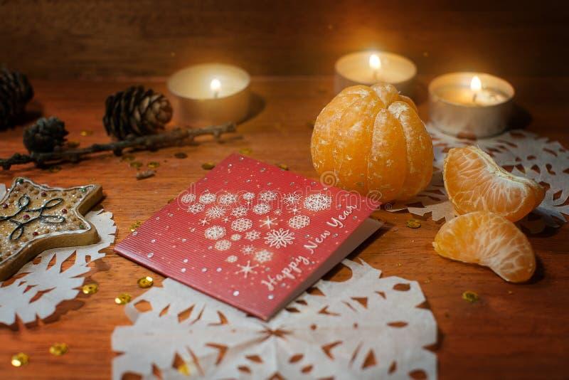 Tarjeta del Año Nuevo con las velas y el mandarín fotografía de archivo libre de regalías