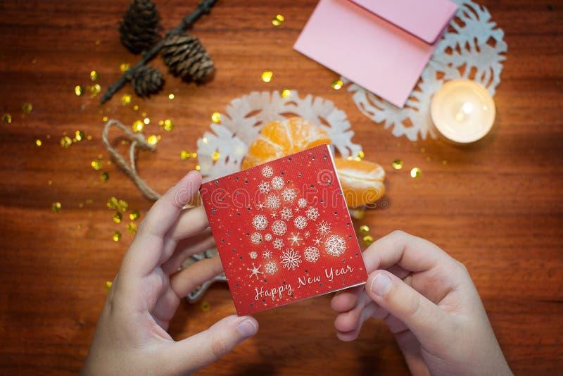 Tarjeta del Año Nuevo en las manos de fotos de archivo libres de regalías