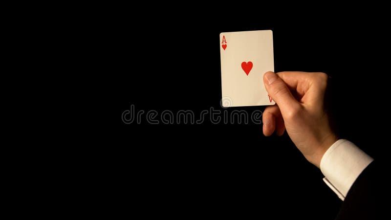 Tarjeta del as de la demostraci?n de la mano en el fondo negro, concepto de suerte en el juego, casino imagenes de archivo