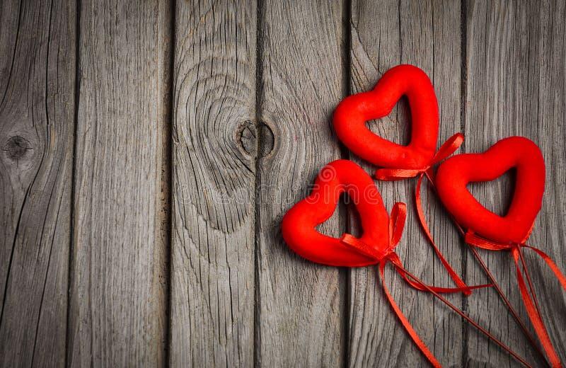 Tarjeta del día de tarjeta del día de San Valentín con tres corazones rojos en fondo de madera rústico fotos de archivo