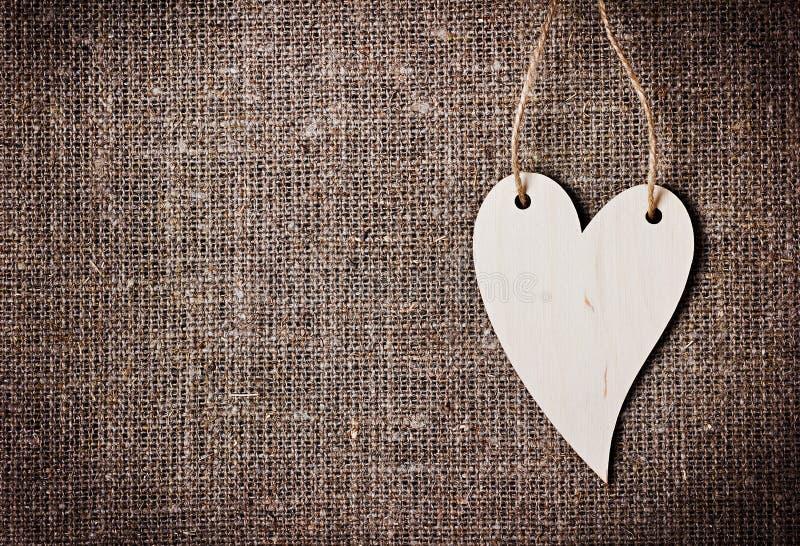 Tarjeta del día de tarjetas del día de San Valentín con los corazones en un despido o un fondo de la arpillera o de la arpillera fotos de archivo