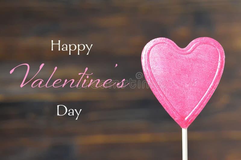 Tarjeta del día de tarjetas del día de San Valentín Piruleta del caramelo del corazón en fondo de madera imagen de archivo libre de regalías