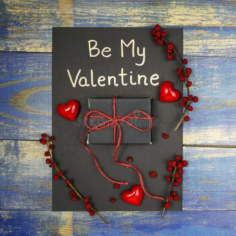 Tarjeta del día del ` s de la tarjeta del día de San Valentín con la caja de regalo, los corazones rojos y las frutas color de ro fotografía de archivo
