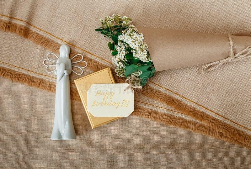Tarjeta del deseo en la actual caja de oro con el ángel de cerámica blanco Flores blancas del ramo pequeñas en papel del arte de  fotografía de archivo