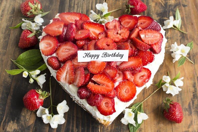 Tarjeta del feliz cumpleaños con el pastel de queso del corazón con las fresas imagen de archivo