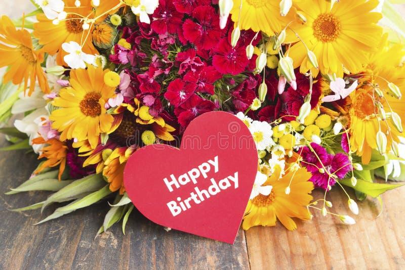 Tarjeta del feliz cumpleaños con las flores de la primavera fotografía de archivo