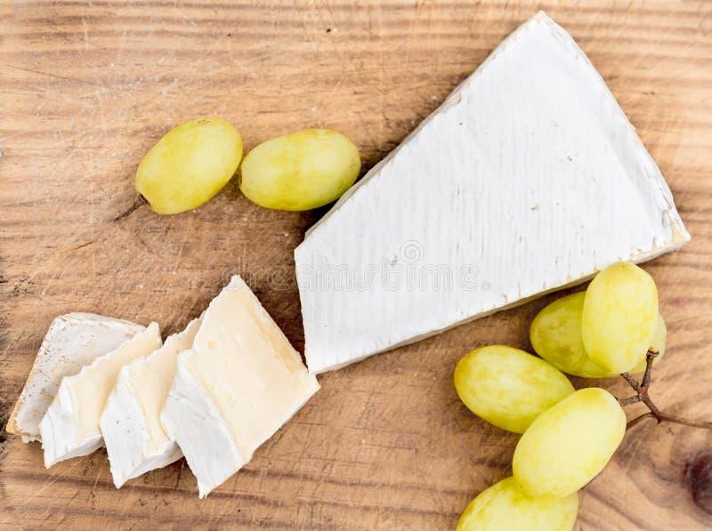 Tarjeta del queso Brie cremoso en tabla de cortar rústica sobre el wo blanco imagen de archivo