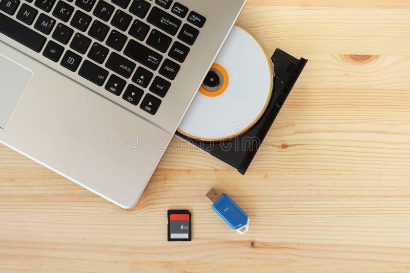 Tarjeta del SD, memoria USB USB3 0 y escritor Burner Reader de la impulsión del DVD del CD del ordenador portátil en fondo de mad imágenes de archivo libres de regalías