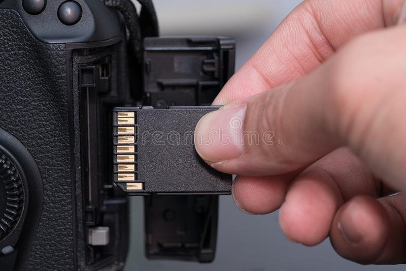 tarjeta del SD del parte movible de la mano in camera foto de archivo