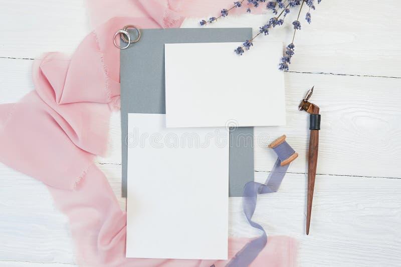 Tarjeta en blanco blanca con dos anillos de bodas en un fondo de la tela rosada con las flores de la lavanda y la pluma caligráfi fotos de archivo libres de regalías