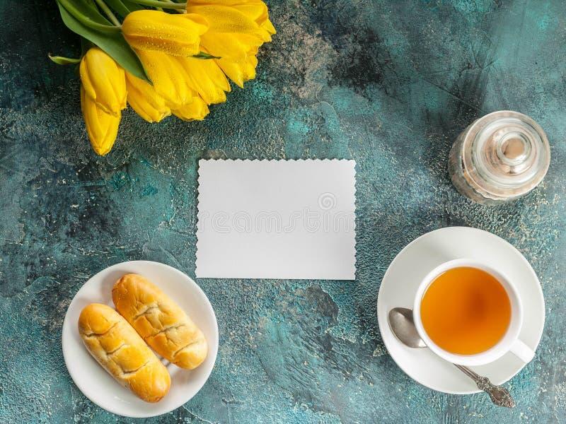 Tarjeta en blanco blanca, tulipanes amarillos, taza de té y tortas en fondo concreto azul Visión superior Copie el espacio fotografía de archivo