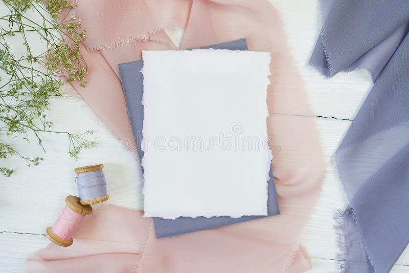 Tarjeta en blanco blanca en un fondo de la tela rosada y azul en un fondo blanco Maqueta con el sobre y la tarjeta en blanco imagen de archivo libre de regalías
