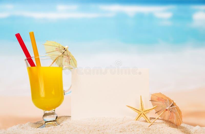 Tarjeta en blanco, cóctel anaranjado de cristal, estrella de mar en arena contra el mar imágenes de archivo libres de regalías