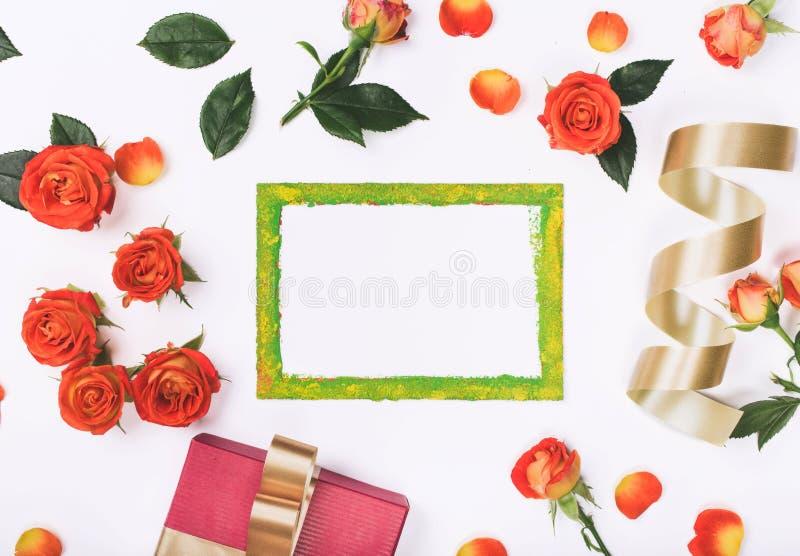 Tarjeta en blanco con las rosas rojas, la caja de regalo y la cinta de oro imágenes de archivo libres de regalías