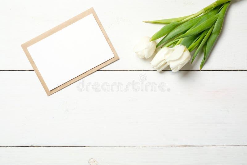 Tarjeta en blanco para la invitación o la enhorabuena con el manojo de flores blancas de los tulipanes en la tabla de madera blan fotografía de archivo