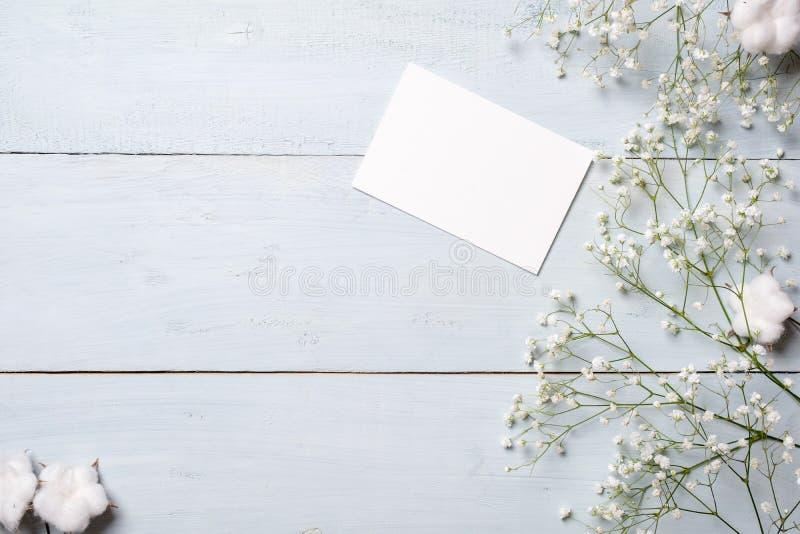 Tarjeta en blanco para la invitación o la enhorabuena, pequeña caja de regalo, manojo de flores del gypsophila en la tabla de mad imagen de archivo