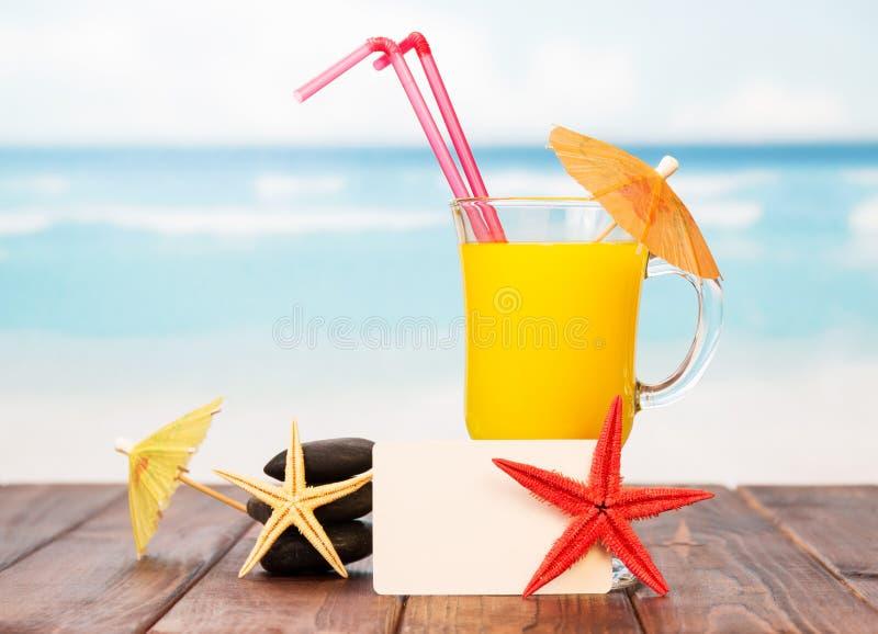 Tarjeta en blanco, vidrio del cóctel anaranjado y estrellas de mar en el mar fotografía de archivo libre de regalías