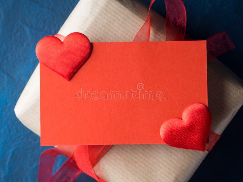 Tarjeta en blanco y regalo rojos con la cinta fotografía de archivo
