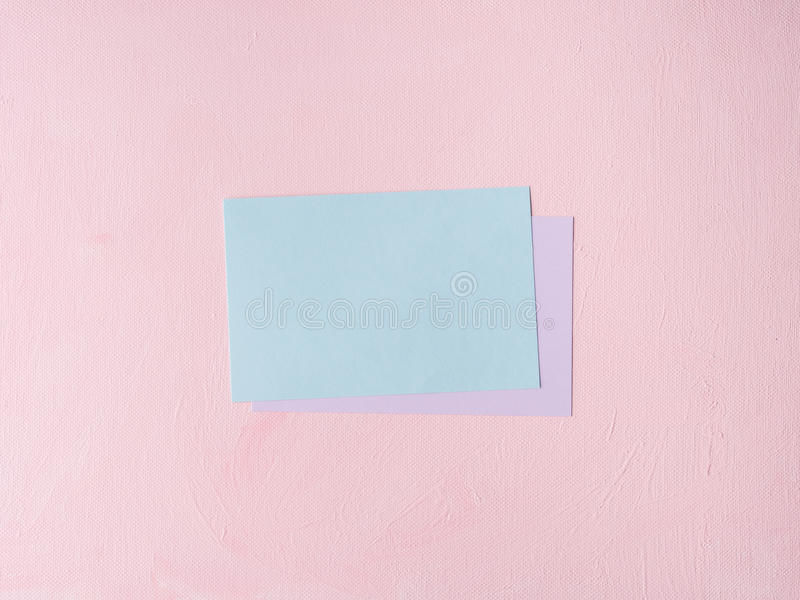 Tarjeta en colores pastel verde en fondo texturizado rosa foto de archivo