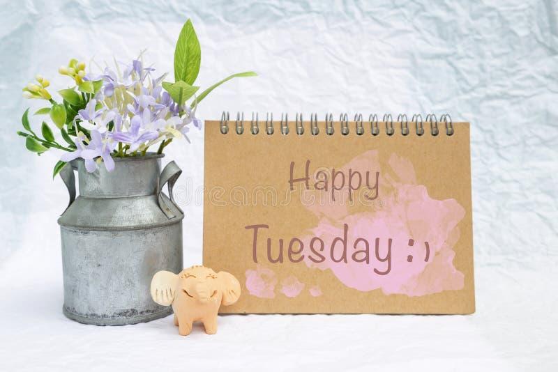 Tarjeta feliz de martes con la pequeñas muñeca de la arcilla del elefante y maceta sonrientes del metal foto de archivo
