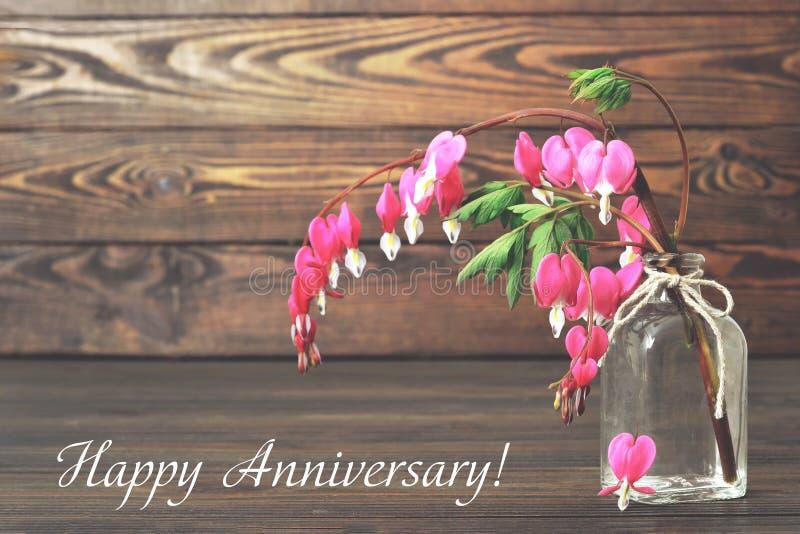 Tarjeta feliz del aniversario con la flor del corazón sangrante en un florero imágenes de archivo libres de regalías