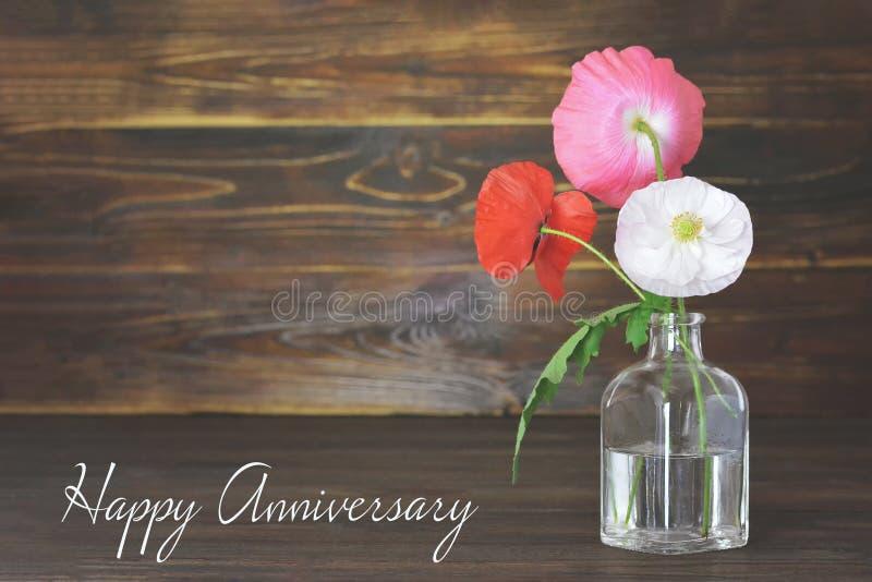 Tarjeta feliz del aniversario con las flores de la amapola en florero imagenes de archivo