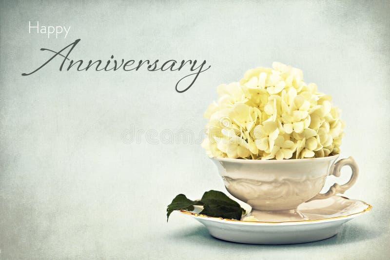 Tarjeta feliz del aniversario Flor de la bola de nieve en taza de t? del vintage foto de archivo