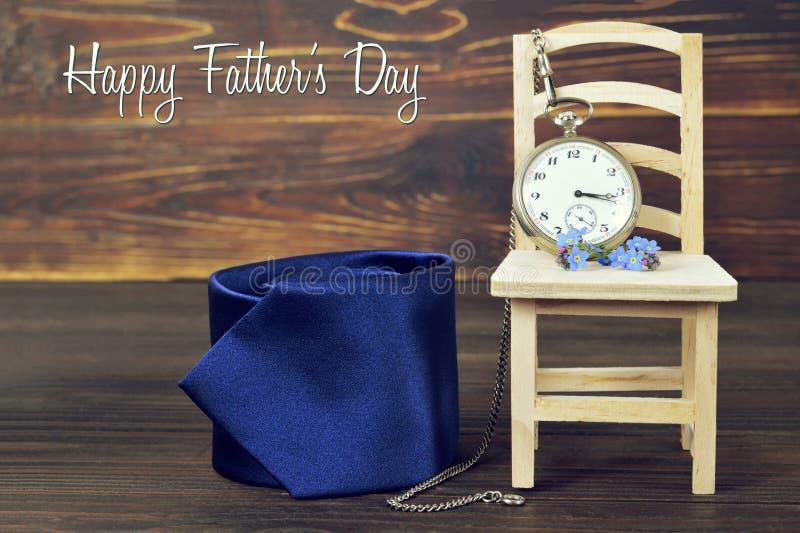 Tarjeta feliz del día de padres con el lazo, el reloj de bolsillo del vintage y las flores fotos de archivo libres de regalías