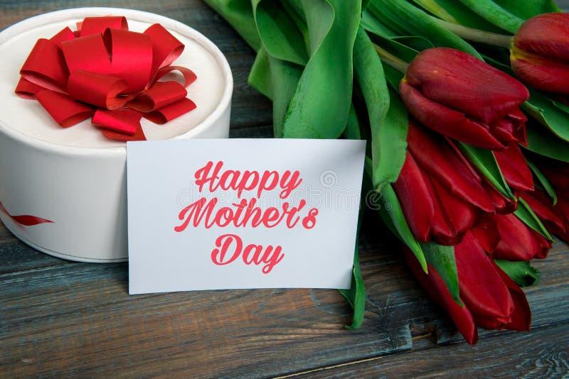 Tarjeta feliz del día del ` s de la madre con los tulipanes rojos fotos de archivo