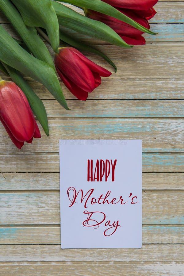 Tarjeta feliz del día del ` s de la madre con los tulipanes rojos imagen de archivo