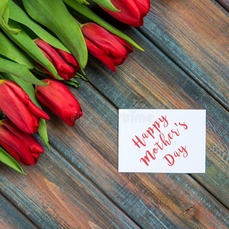Tarjeta feliz del día del ` s de la madre con los tulipanes rojos foto de archivo