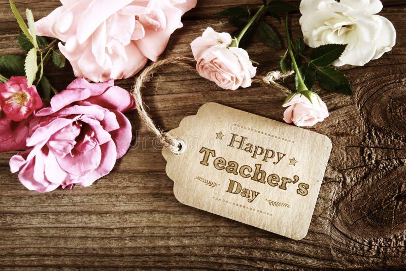 Tarjeta feliz del mensaje del día de los profesores con las pequeñas rosas foto de archivo libre de regalías
