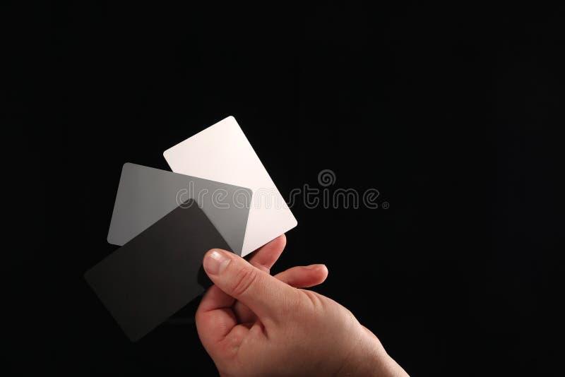 Tarjeta gris Juego de tarjetas de color blanco, negro y gris 18% para ajustar el balance de blancos digital en un brazo macho sob fotos de archivo libres de regalías
