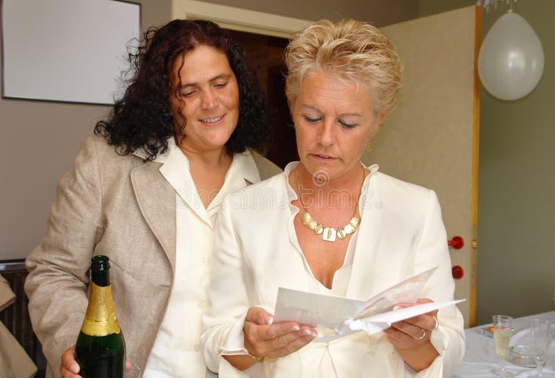 Tarjeta lesbiana de la enhorabuena de la unión de la lectura de los pares imagen de archivo