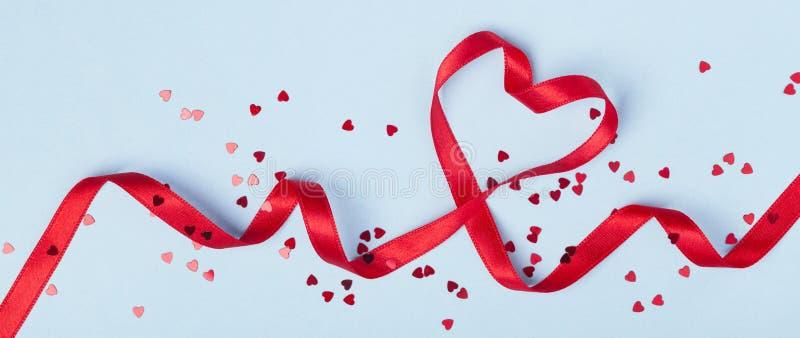 Tarjeta o bandera del día de San Valentín Corazón rojo de la cinta en fondo azul Endecha plana imagenes de archivo